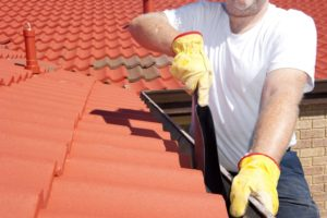 Man Cleaning Roof Gutter