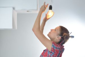 Woman installing a lightbulb