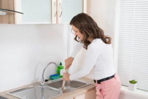 Woman Using Plunger in Kitchen Sink