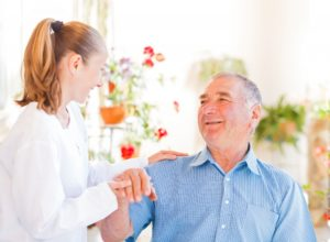 Caregiver assisting a senior man with Dementia