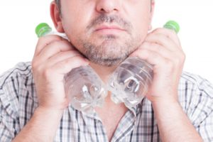 Man cooling himself with two cold water bottles