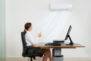 Woman turning her office air conditioner on