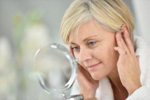 Woman inspecting her face through a face mirror