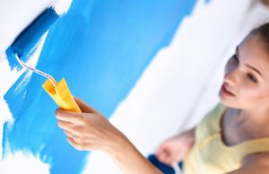 Woman repainting their house wall