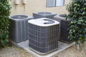 Residential air conditioner compressor units near building
