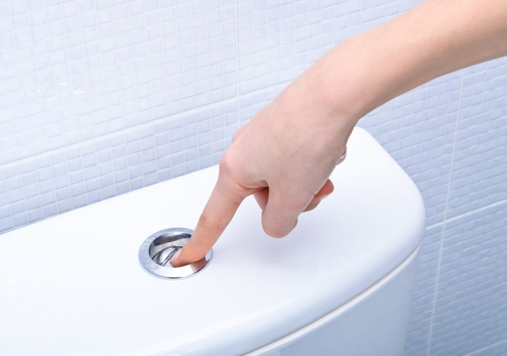 Finger pushing button to flush toilet