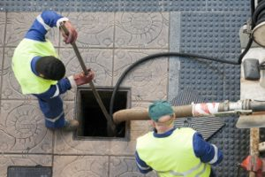workers cleaning the sewer line