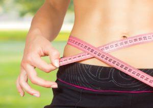 slim female measuring her waste