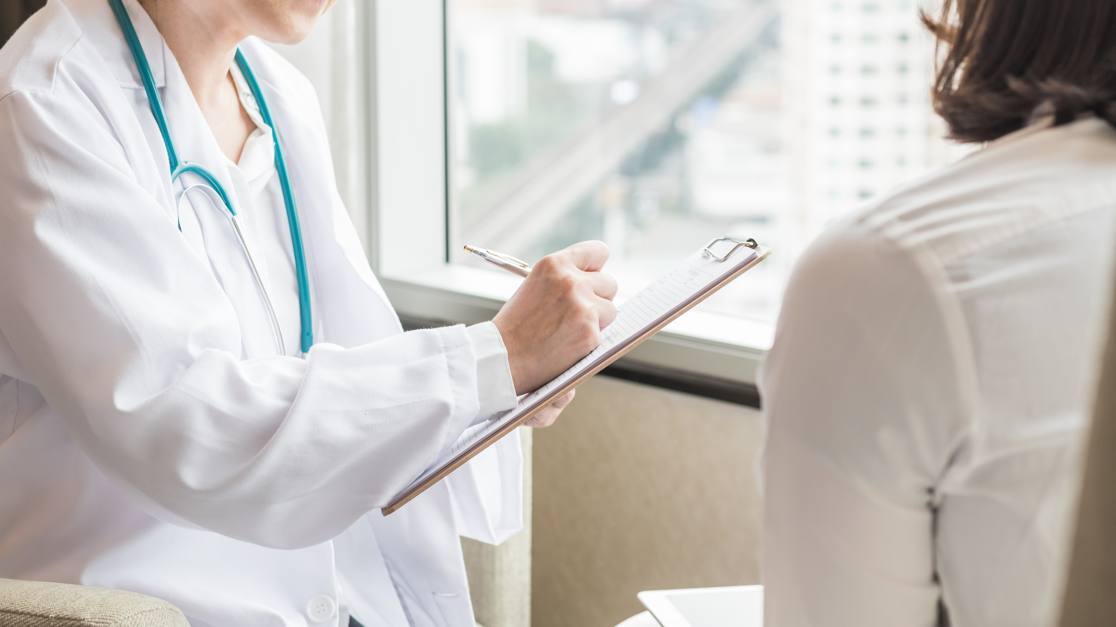a doctor writing on her clipboard