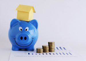 Piggy bank with house model and stacked coins