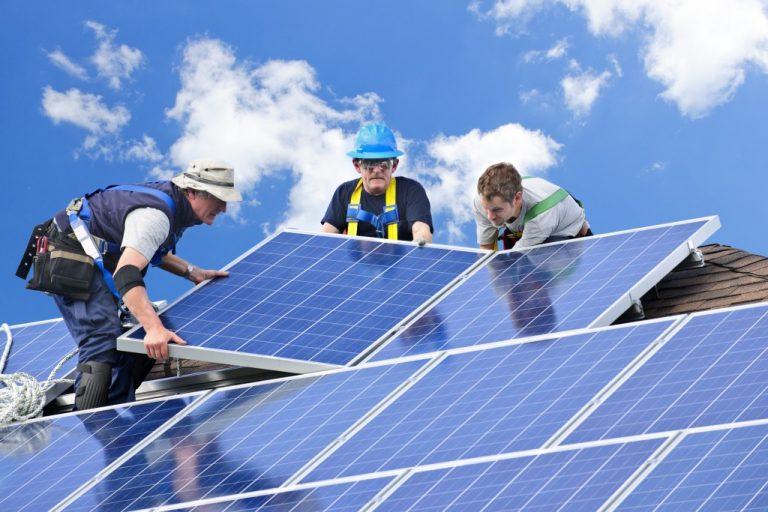 Men putting solar panels on roof