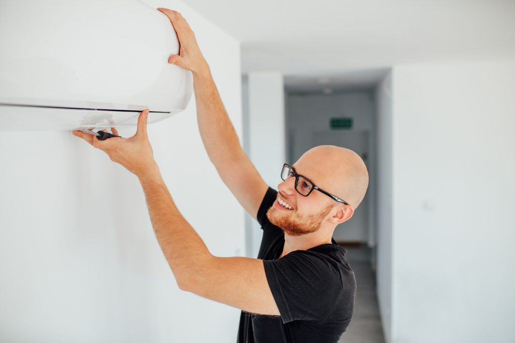 Guy fixing the air conditioning unit