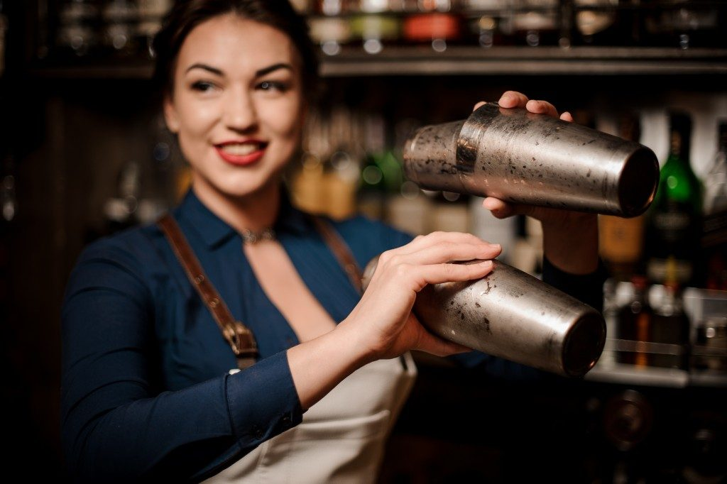 bartender girl in the white apron holding in her hands two steel cocktail shakers