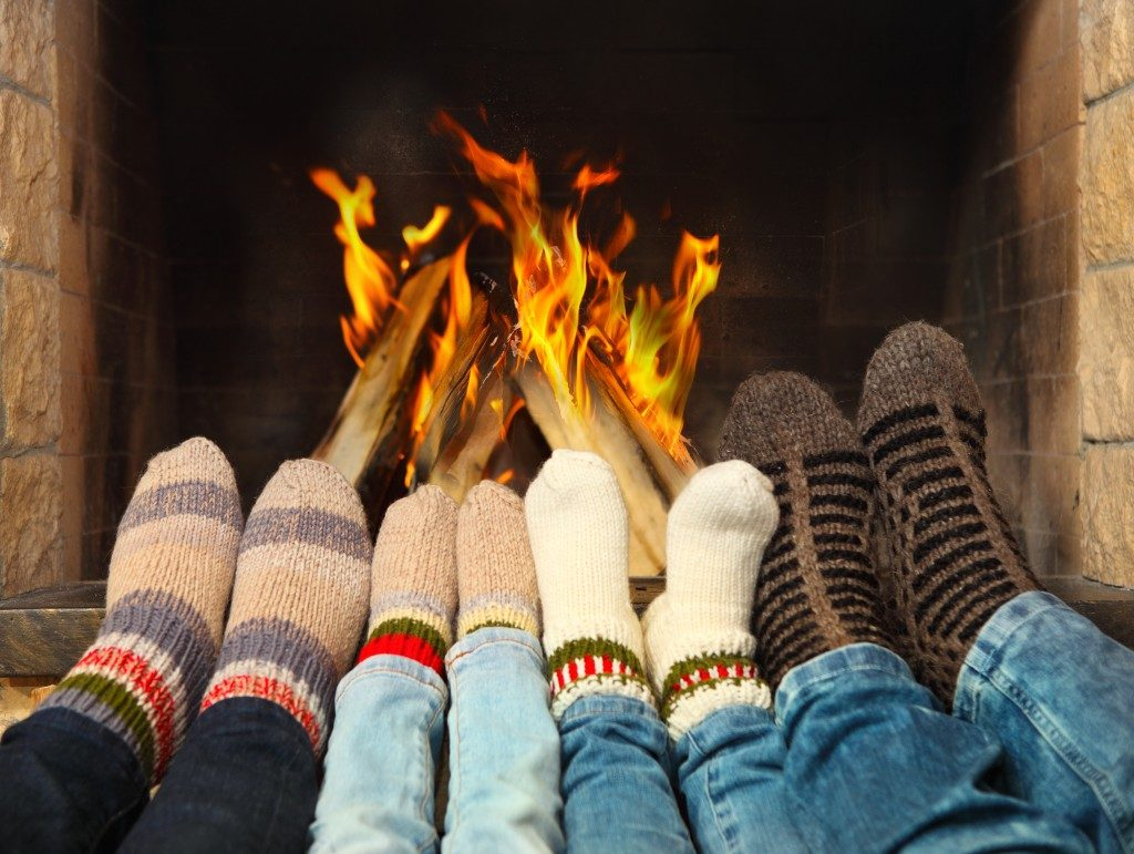 family wearing woolen socks warming near the fireplace