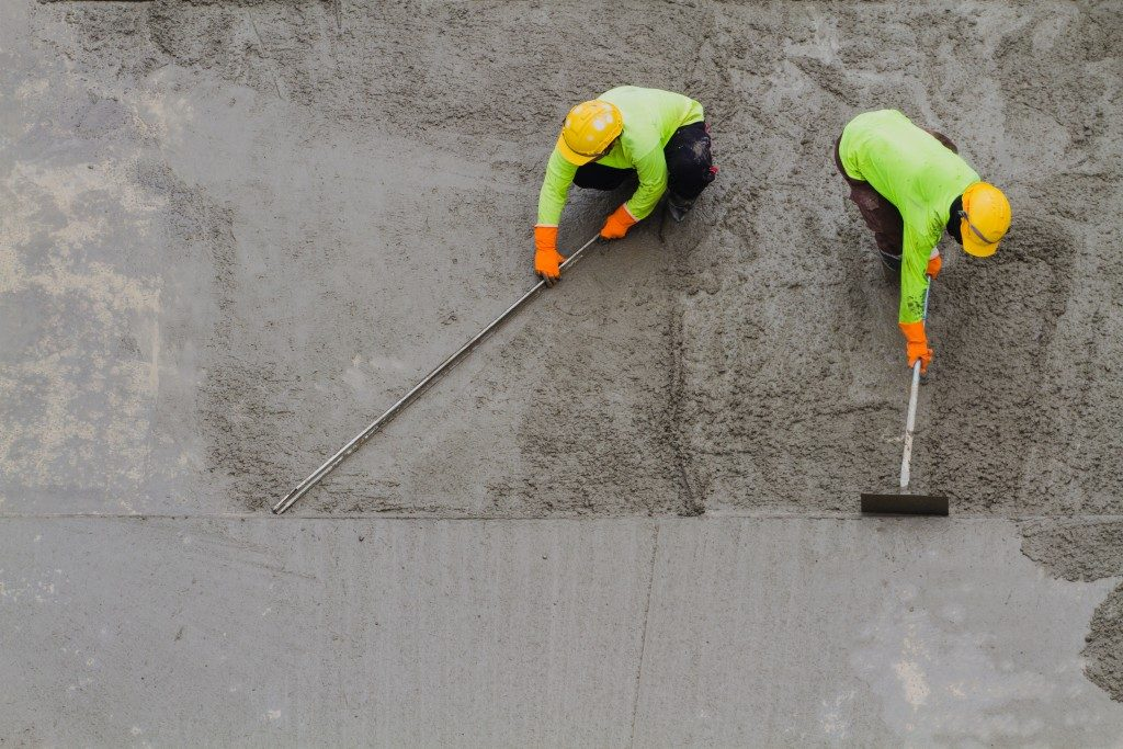 Men fixing wet cement