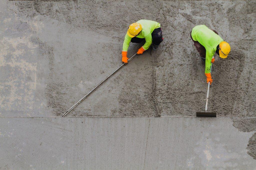 Men fixing wet cement