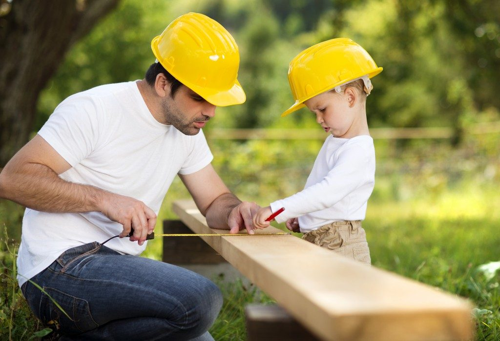 son helping his father with building work