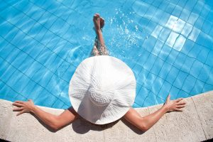 Woman wearing a big hat in a swimming pool