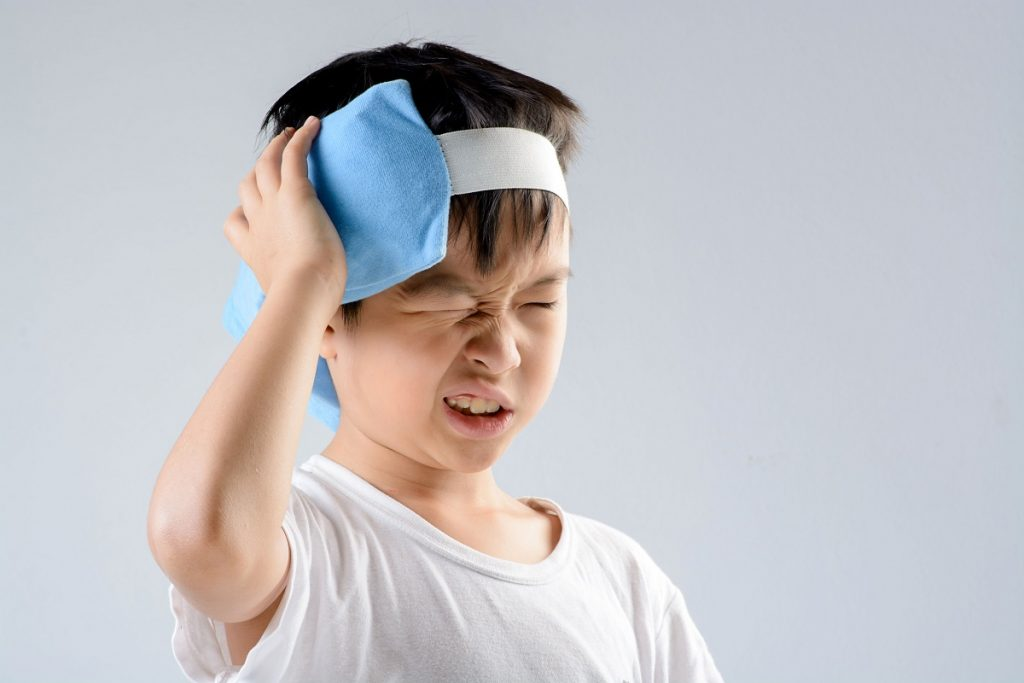 Child applying hot compress on his ear