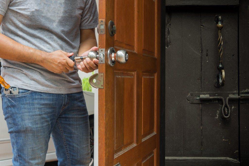 man fixing lock system of door