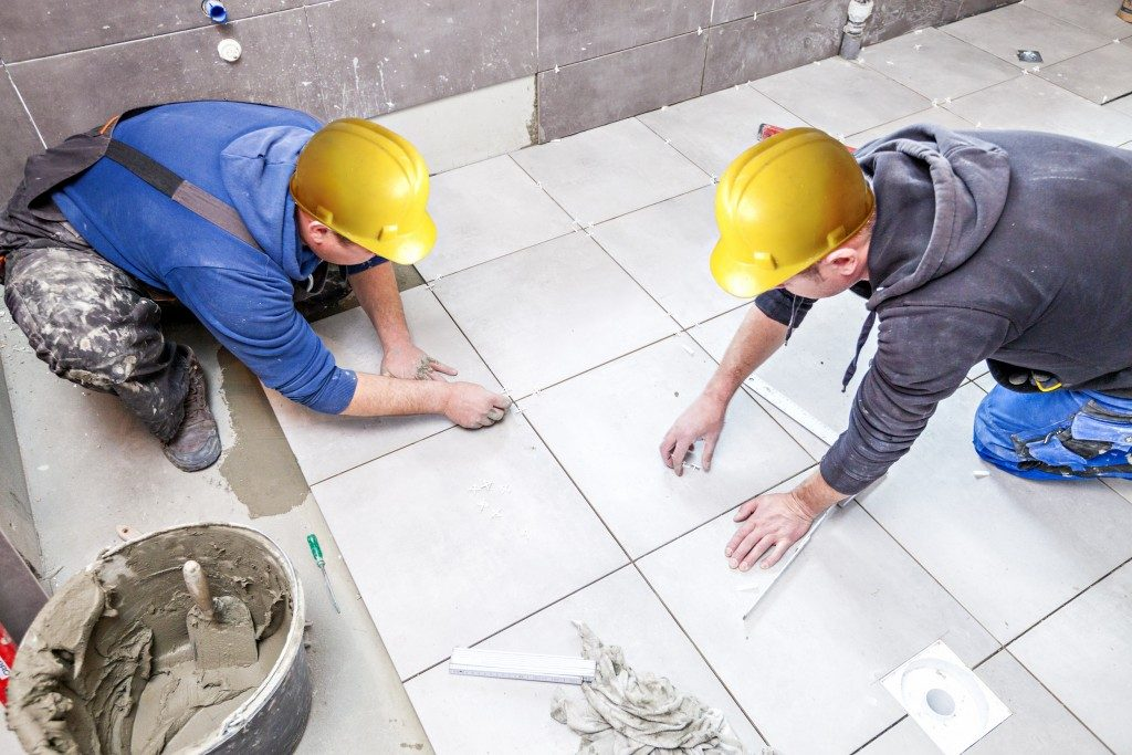Men removing the grout lines