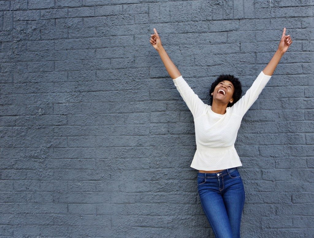Confident woman raising her hands