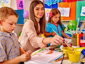 a teacher guiding her students in their art class