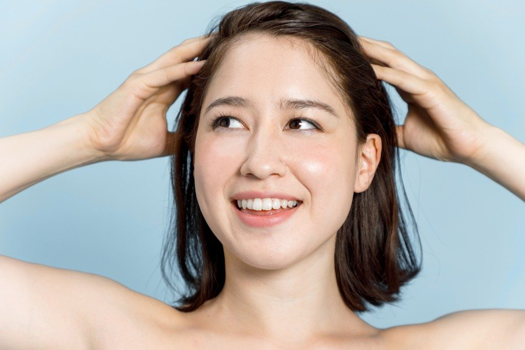 beautiful woman massaging her head. scalp massage. lymphatic massage.