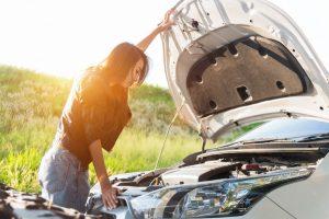 Woman opening car hood