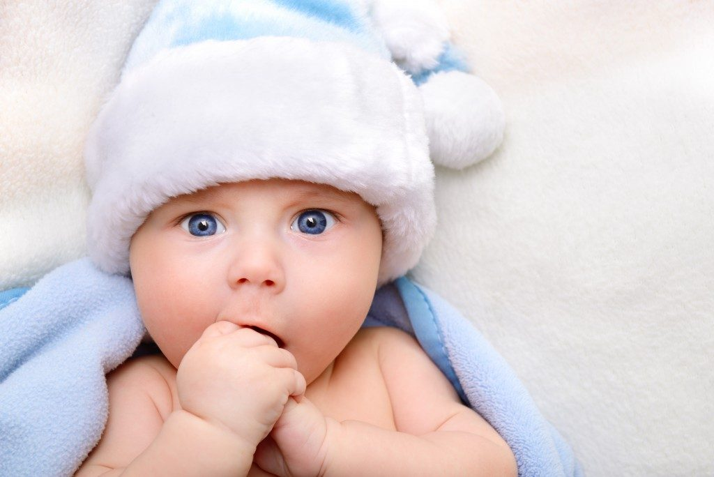 baby wearing blue fuzzy hat
