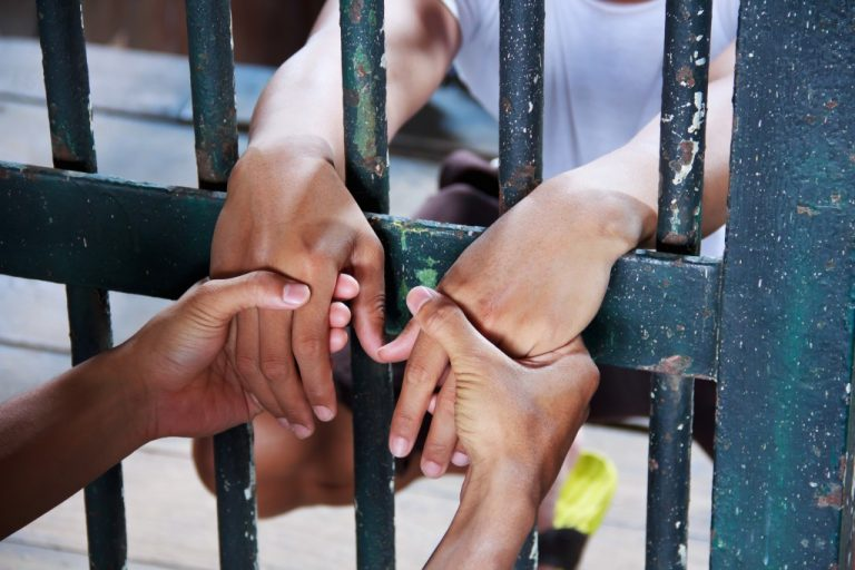 person holding a man's hand inside a jail cell