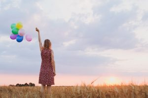 woman staring at the sun while holding colorful balloons