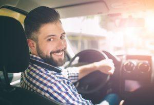 man inside his car smiling