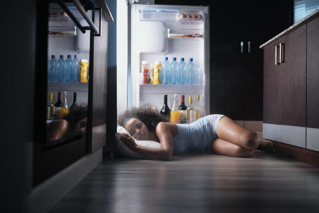 woman sleeping near an open fridge