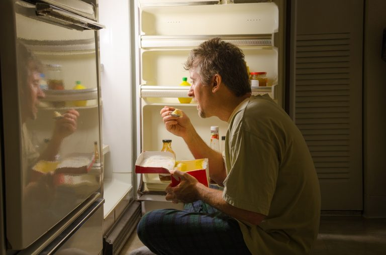 man binge eating in front of the refrigerator