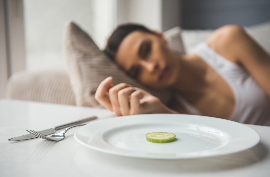 Woman in bed suffering from an eating disorder