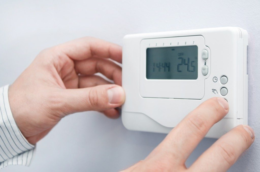 person adjusting the thermostat
