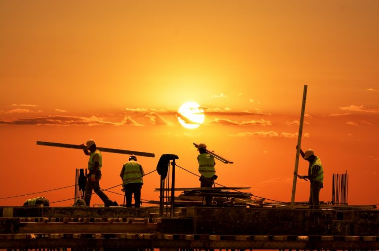 workers constructing building during the sunset