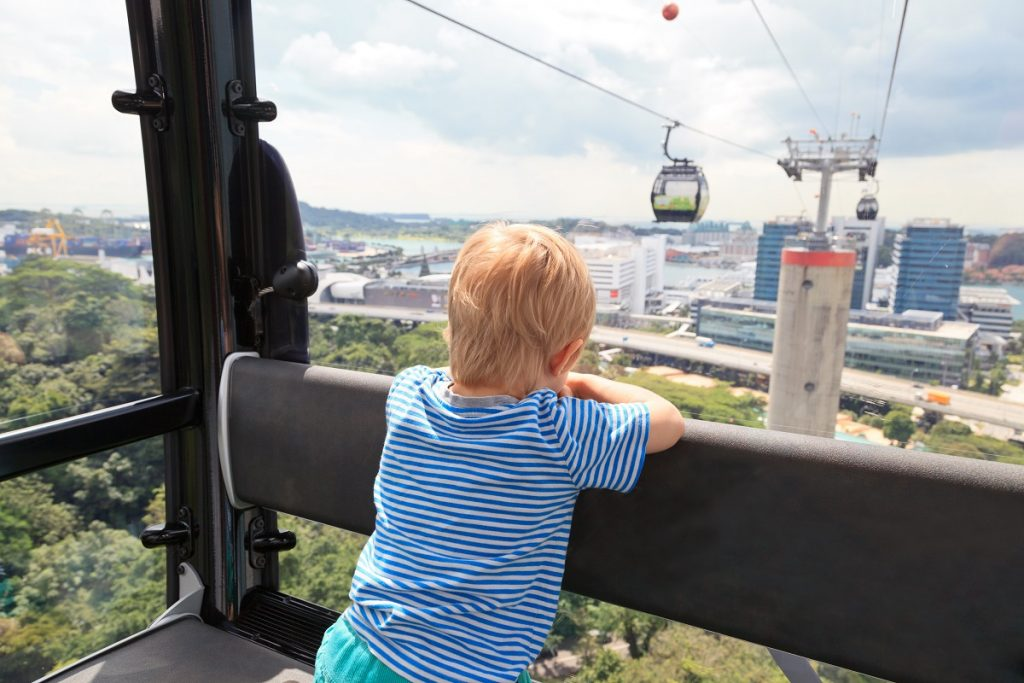 young kid riding a cable car