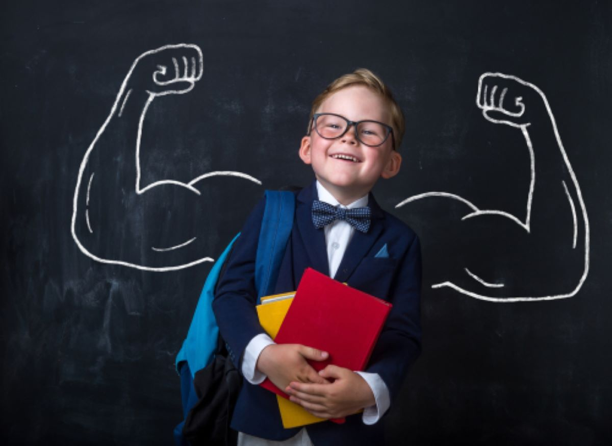 boy with muscular biceps drawn behind him on a chalkboard
