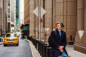 man sitting on bollard by the sidewalk